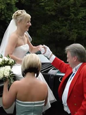 English toastmaster assisting a bride from a horse drawn carraige